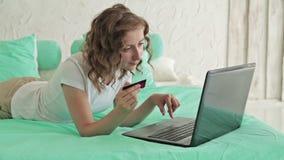 Donna che compera online al computer portatile con la carta di credito video d archivio