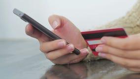 Donna che compera online allo smartphone con la carta di credito archivi video