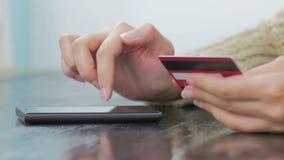 Donna che compera online allo smartphone con la carta di credito stock footage