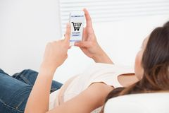 Donna che compera online sul telefono cellulare a casa Fotografie Stock