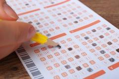 Donna che compila il biglietto di lotteria di matita sulla tavola di legno, primo piano immagine stock libera da diritti