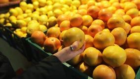 Donna che compra gli agrumi freschi - pompelmi al supermercato Concetto organico e di sanità di consumismo, di vendita, archivi video