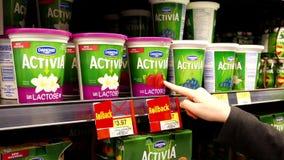 Donna che compra il yogurt della fragola di Danone Activia stock footage