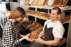 Donna che compra pasticceria saporita in forno immagini stock