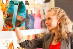 Donna che compra una borsa in centro commerciale Fotografie Stock