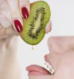 Donna che comprime kiwi nella bocca Immagine Stock Libera da Diritti
