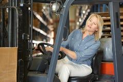 Donna che conduce carrello elevatore a forcale in magazzino Fotografia Stock