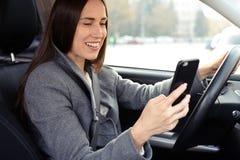 Donna che conduce l'automobile e che per mezzo del suo smartphone Immagini Stock