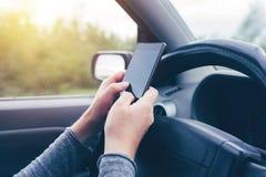 Donna che conduce simultaneamente automobile e che scrive messaggio di testo a macchina Fotografia Stock Libera da Diritti