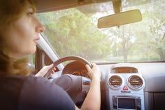 Donna che conduce un'automobile, vista da dietro fotografia stock