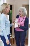 Donna che consegna giornale al vicino anziano Immagine Stock