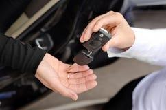 Donna che consegna un insieme delle chiavi dell'automobile Fotografie Stock Libere da Diritti