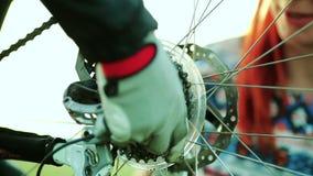 Donna che contribuisce a riparare la sua bici archivi video