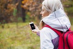 Donna che controlla bussola app sul suo smartphone fotografia stock libera da diritti