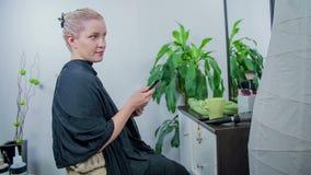 Donna che controlla come lo styler dei capelli è fatto il suo lavoro video d archivio