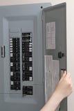 Donna che controlla i fusibili automatici al pannello di controllo elettrico Immagini Stock Libere da Diritti