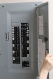Donna che controlla i fusibili automatici al pannello di controllo elettrico Fotografia Stock Libera da Diritti
