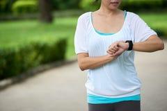 Donna che controlla il braccialetto di forma fisica Immagini Stock Libere da Diritti