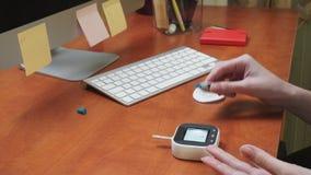 Donna che controlla il livello della glicemia con un metro del glucosio con goccia del sangue