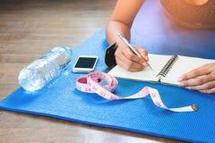 Donna che controlla la sua salute dopo l'allenamento, la dieta e la forma fisica Fotografia Stock