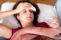 Donna che controlla la sua temperatura corporea Fotografia Stock Libera da Diritti
