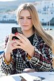Donna che controlla massaggio sul telefono Fotografia Stock Libera da Diritti