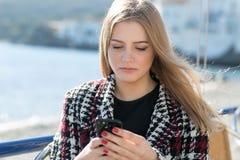 Donna che controlla massaggio sul telefono Fotografie Stock