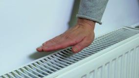 Donna che controlla temperatura del radiatore di riscaldamento