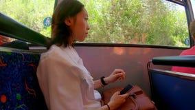 Donna che controlla tempo mentre facendo uso del telefono cellulare 4k archivi video