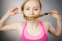 Donna che copre la sua bocca di treccia bionda fotografia stock libera da diritti