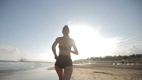 Donna che corre da solo al tramonto bello sulla spiaggia stock footage