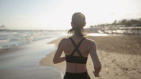 Donna che corre da solo al tramonto bello sulla spiaggia archivi video