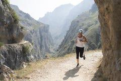 Donna che corre giù il percorso con gli occhiali da sole sull'itinerario delle cure fotografie stock