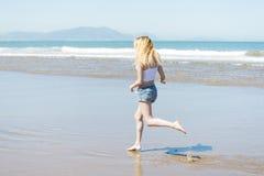 Donna che corre giù la spiaggia nella stagione estiva fotografia stock libera da diritti