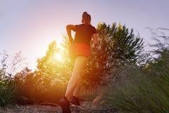 Donna che corre nelle montagne al tramonto immagine stock libera da diritti
