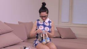 Donna che cuce vecchia bambola sul sofà