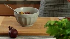 Donna che cucina a casa - il soupl del pouriong nella ciotola archivi video