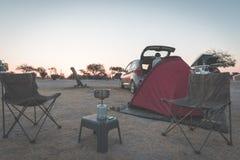 Donna che cucina con la stufa di gas in campeggio al crepuscolo Bruciatore a gas, vaso e fumo da acqua bollente, tenda nei preced immagini stock libere da diritti
