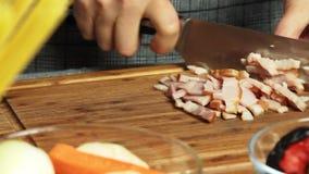 Donna che cucina e che taglia bacon stock footage