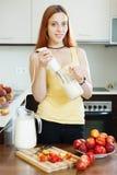 Donna che cucina le bevande della latteria con le nettarine Fotografia Stock