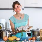 Donna che cucina pesce in cucina Fotografia Stock Libera da Diritti