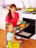 Donna che cucina pollo alla cucina. Fotografia Stock
