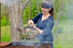Donna che cucina sopra un BBQ che reagisce nell'orrore Fotografia Stock Libera da Diritti