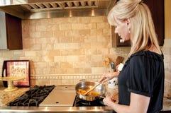 Donna che cucina su un intervallo di gas Fotografia Stock