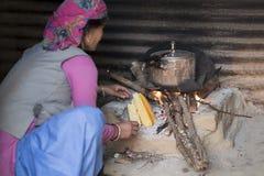 Donna che cucina sul fuoco di legno fotografia stock libera da diritti