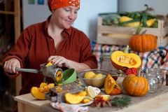 Donna che cucina zucca alla sua cucina Fotografie Stock Libere da Diritti