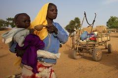 Donna che dà acqua al suo bambino nel Mali fotografia stock libera da diritti