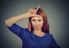Donna che dà il segno del perdente sulla fronte, esaminante vi Immagini Stock