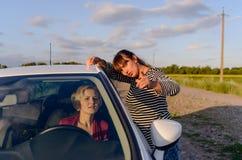 Donna che dà le indicazioni ad un driver femminile Fotografia Stock Libera da Diritti