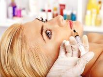 Donna che dà le iniezioni del botox. Fotografia Stock
